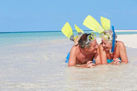 senior-couple-snorkels-enjoying-beach-holiday-smiling-image29820731